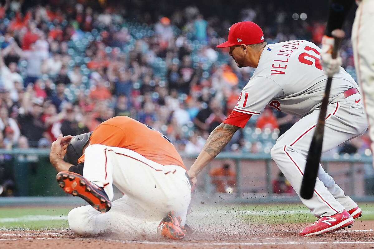 SAN FRANCISCO, CALIFORNIA - JUNE 18: Jason Vosler #32 of the San Francisco Giants slides past Vince Velasquez #21 of the Philadelphia Phillies to score during the second inning at Oracle Park on June 18, 2021 in San Francisco, California. (Photo by Ben Green/Getty Images)