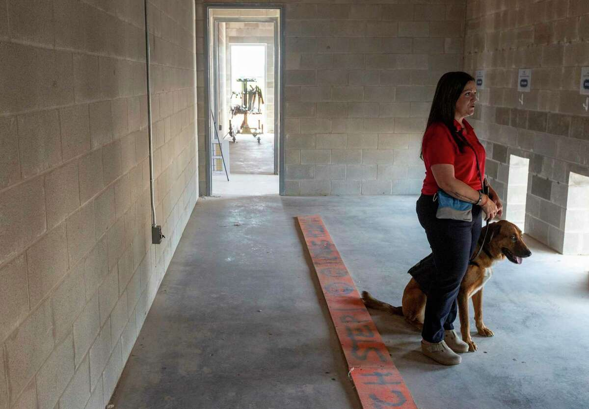 """Service dog """"Javie"""" sits with his owner, Shilo Schluterman, in the future kennel area of the Petco Love K9 Center building under construction."""