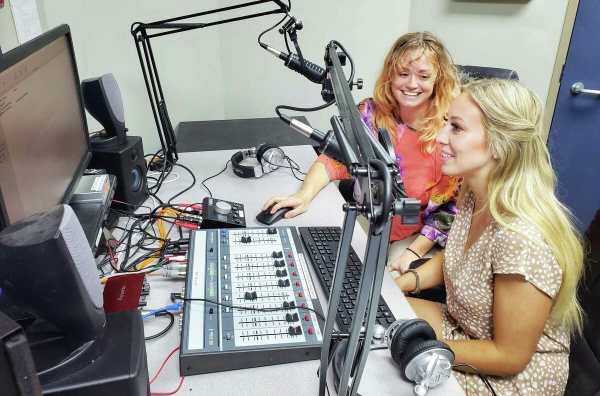 Marketing and Tourism Specialist Larrissa Roberts instructs summer marketing intern Kennedy Thompson on the workings of the studio and station programming as they sit at the console at Tomball's own low power FM radio station KTTF 95.3 FM. Roberts will graduate from Texas A&Mnext spring with a degree in communications.