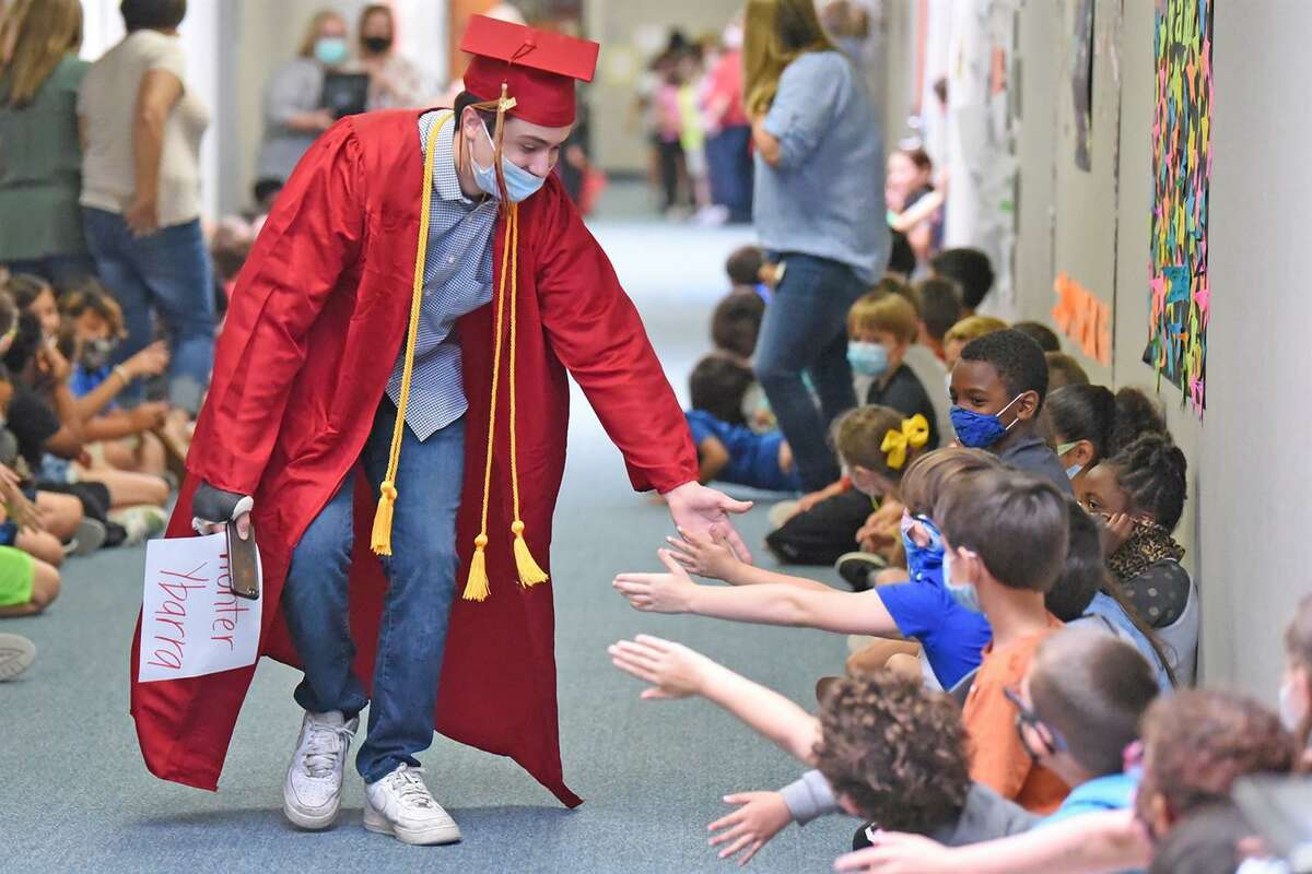 Cypress Woods High School graduate Hunter Ybarra interacts with A. Robison Elementary School students during a senior walk at the campus on May 27. Many CFISD elementary schools and some middle schools welcomed back graduating seniors in the final weeks of the school year. The graduates wore their caps, gowns and honor cords, walking through crowded halls of cheering students.