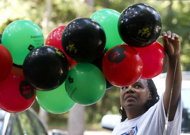 Tasia Payne helps hang Juneteenth-themed balloons during a celebration at Kasmiersky Park, Saturday, June 19, 2021, in Conroe. Juneteenth, which recently became a federal holiday after being signed into law this week by President Joe Biden, recognizes the end of slavery in the United States. It is held on June 19, the anniversary of the announcement of emancipation for enslaved people in Texas in 1865, nearly three years after President Abraham Lincoln signed the Emancipation Proclamation. Photo: Jason Fochtman/Staff Photographer / 2021 © Houston Chronicle