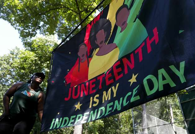 Tasia Payne hangs a Juneteenth flag during a Juneteenth celebration at Kasmiersky Park, Saturday, June 19, 2021, in Conroe. Juneteenth, which recently became a federal holiday after being signed into law this week by President Joe Biden, recognizes the end of slavery in the United States. It is held on June 19, the anniversary of the announcement of emancipation for enslaved people in Texas in 1865, nearly three years after President Abraham Lincoln signed the Emancipation Proclamation. Photo: Jason Fochtman/Staff Photographer / 2021 ? Houston Chronicle