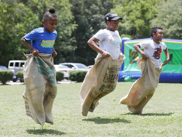 Santana Johnson, left, competes in a sack race against Charnesha Carter and Devin Wright during a Juneteenth celebration at Kasmiersky Park, Saturday, June 19, 2021, in Conroe. Juneteenth, which recently became a federal holiday after being signed into law this week by President Joe Biden, recognizes the end of slavery in the United States. It is held on June 19, the anniversary of the announcement of emancipation for enslaved people in Texas in 1865, nearly three years after President Abraham Lincoln signed the Emancipation Proclamation. Photo: Jason Fochtman/Staff Photographer / 2021 © Houston Chronicle