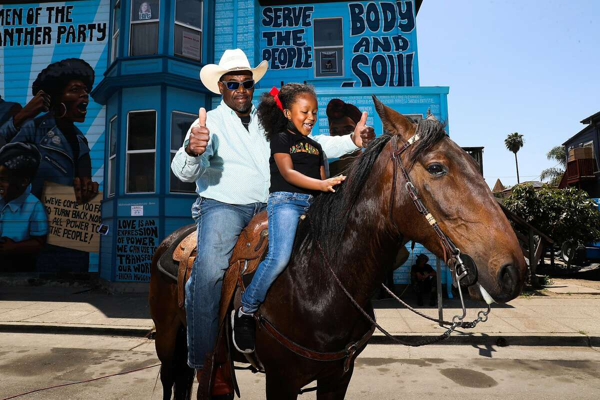 Donnell McAlister of Vallejo gives a thumbs-up as Dakota Lane, 6, of San Pablo pets his horse JJ during Oakland's Juneteenth celebration.