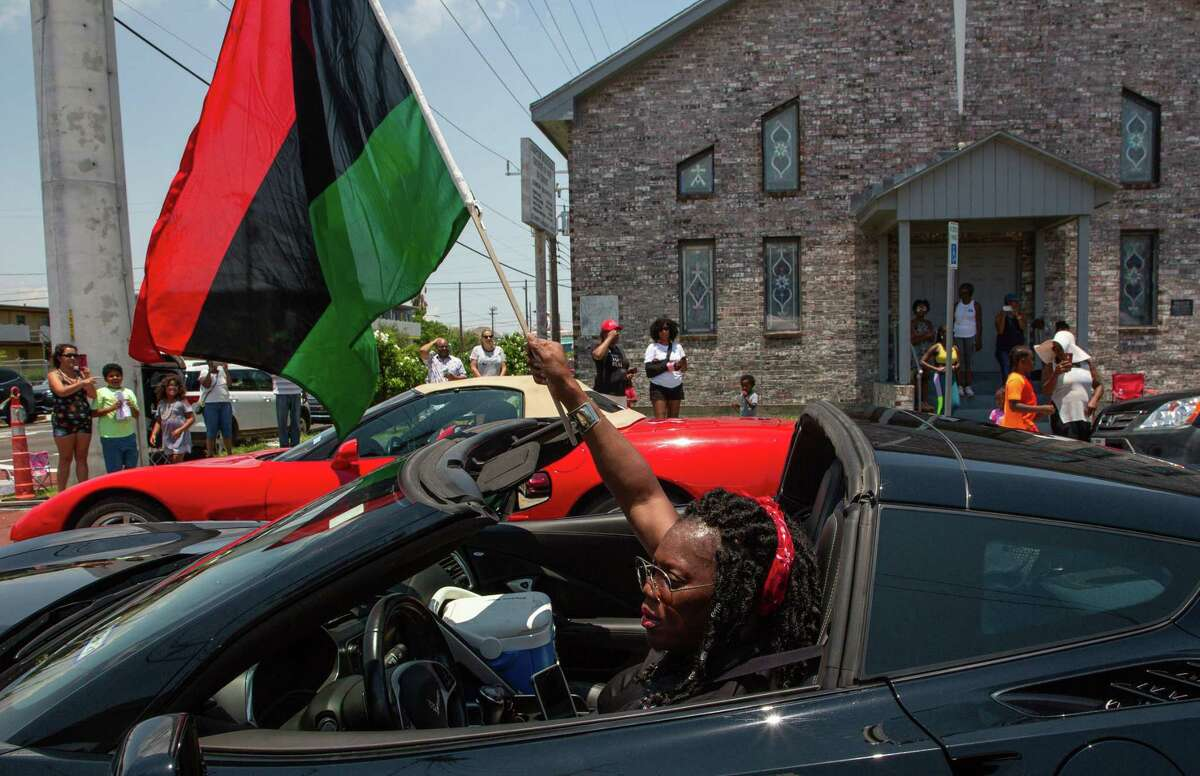 Savannah Taplin waves a Black Liberation flag while participating in the Juneteenth Parade on Ball Street on June 19, 2021, in Galveston.