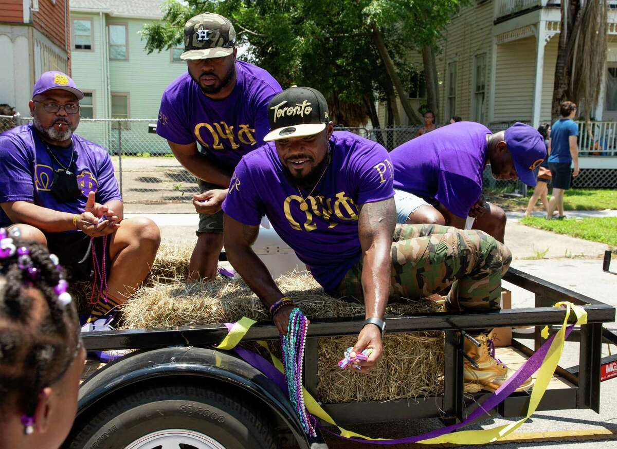 Members of the Omega Psi Phi fraternity hand out candy to children during the Juneteenth Parade on Ball Street on June 19, 2021, in Galveston.