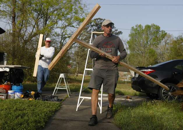"""Allan Schneider carries a support brace in front of Mark Langenberg while helping repair Delia Brown's water-damaged home from February'€™s arctic blast, Tuesday, March 23, 2021, in Conroe. They'€™ve been such a blessing to me€"""" Brown said. """"I don't know what I would have done without them.€ Schneider and Neuberger are part of The Woodlands United Methodist Church's 60-member 'Geezer Group,'€™ a group of volunteers help those in need with small construction projects usually after natural disasters. Photo: Jason Fochtman/Staff Photographer / 2021 © Houston Chronicle"""