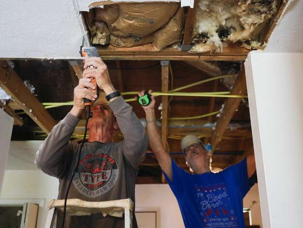 """Allan Schneider, left, cuts drywall as Jerry Neuberger measures a wall while helping repair Delia Brown'€™s water-damaged home from February'€™s arctic blast, Tuesday, March 23, 2021, in Conroe. €˜They'€™ve been such a blessing to me€"""" Brown said. """"I don't know what I would have done without them.€ Schneider and Neuberger are part of The Woodlands United Methodist Church's 60-member 'Geezer Group,'€™ a group of volunteers help those in need with small construction projects usually after natural disasters. Photo: Jason Fochtman/Staff Photographer / 2021 © Houston Chronicle"""