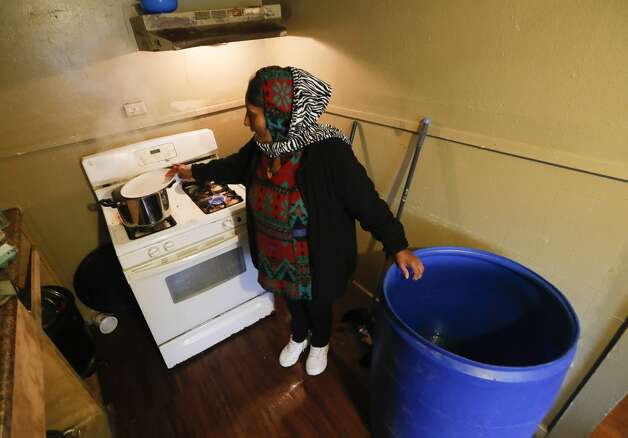 Rosa Martinez melts snow to put in a blue bin to use for water after a pair of pipe bursts cut of water to her home, Thursday, Feb. 18, 2021, in Conroe. Photo: Jason Fochtman/Staff Photographer / 2021 © Houston Chronicle