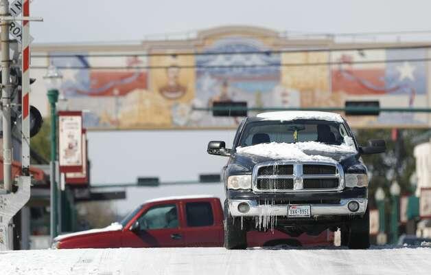 Vehicles drive down West Davis Street through ice and snow, Tuesday, Feb. 16, 2021, in Conroe. Photo: Jason Fochtman/Staff Photographer / 2021 © Houston Chronicle