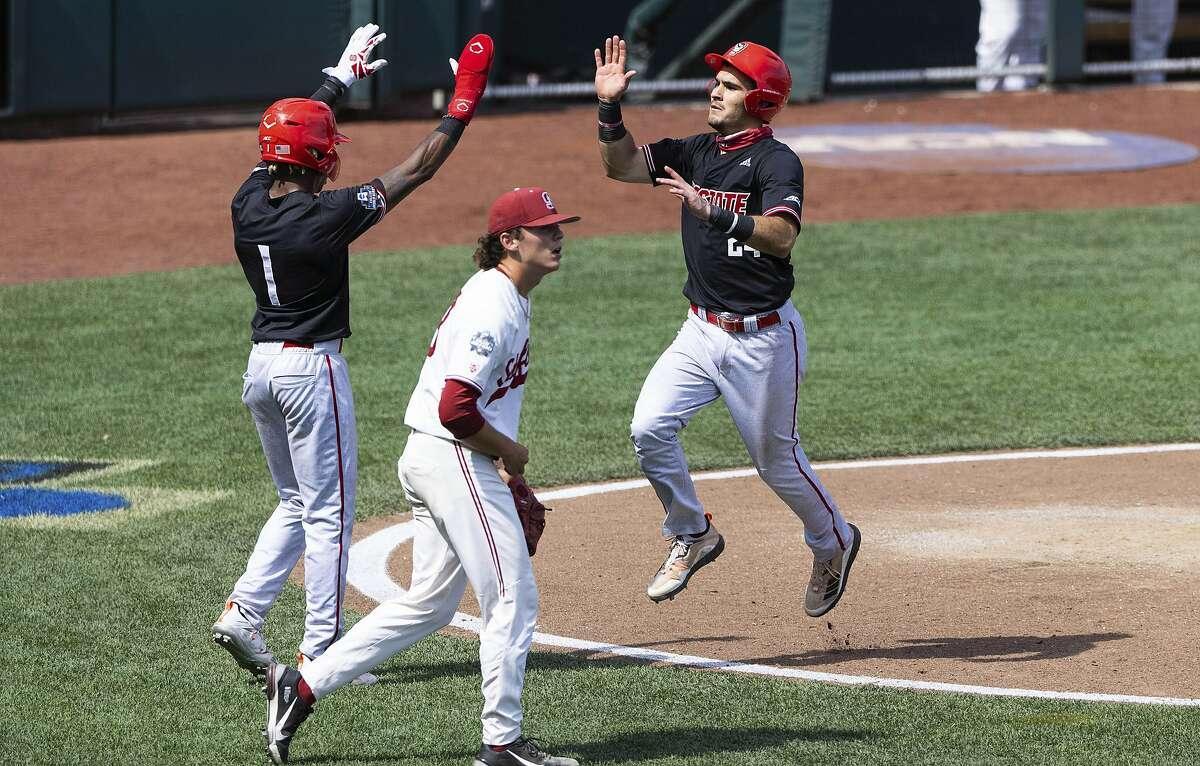 North Carolina State's Terrell Tatum (1) and Luca Tresh (24) celebrate after scoring off an RBI single by Vojtech Mensik (6) in the ninth inning in the opening baseball game against Stanford at the College World Series, Saturday, June 19, 2021, at TD Ameritrade Park in Omaha, Neb. (AP Photo/Rebecca S. Gratz)