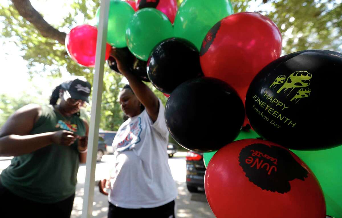 Tasia Payne, left, and her mother hang balloon during a Juneteenth celebration at Kasmiersky Park, Saturday, June 19, 2021, in Conroe. Juneteenth, which recently became a federal holiday after being signed into law this week by President Joe Biden, recognizes the end of slavery in the United States. It is held on June 19, the anniversary of the announcement of emancipation for enslaved people in Texas in 1865, nearly three years after President Abraham Lincoln signed the Emancipation Proclamation.