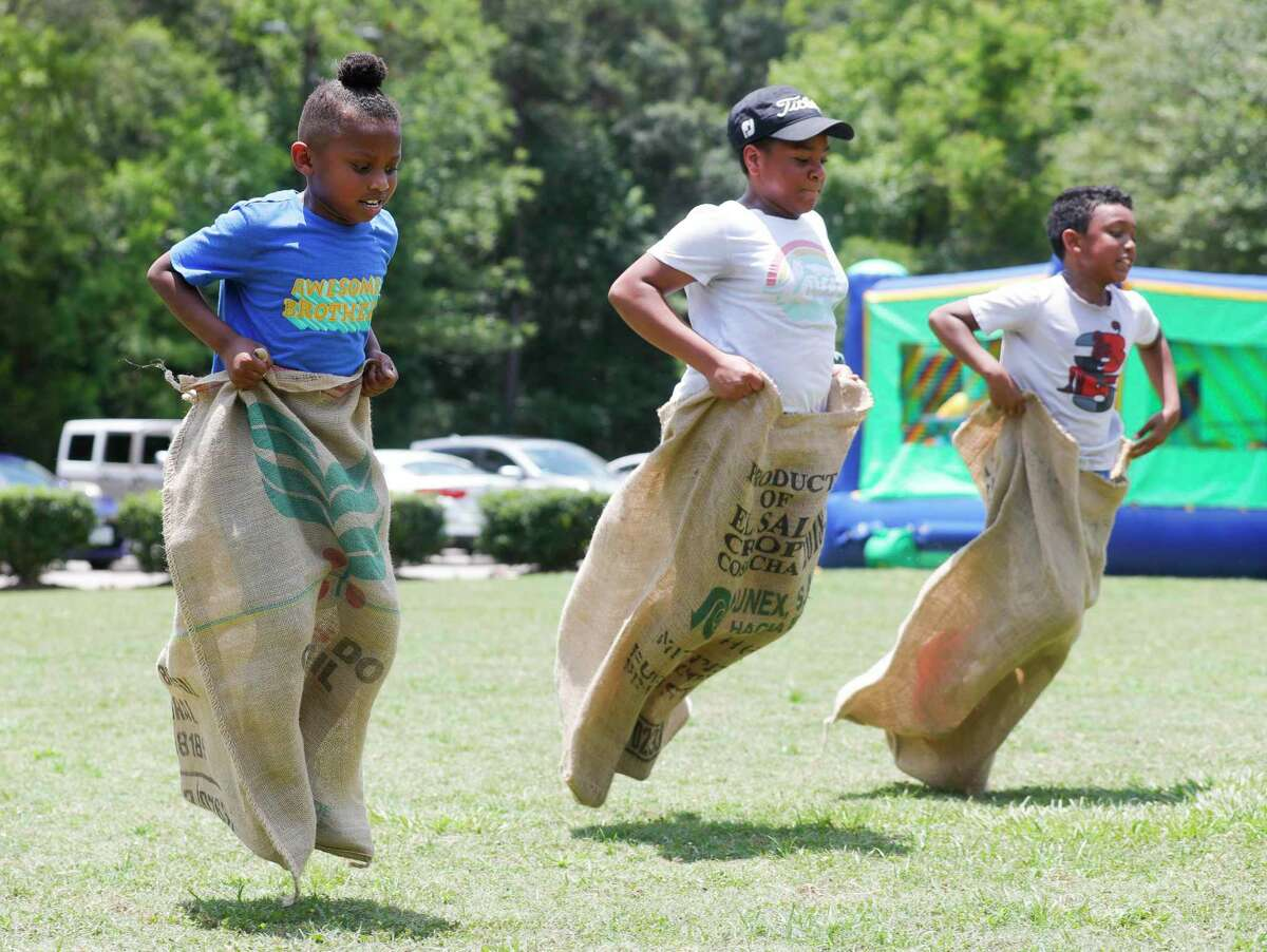 Santana Johnson, left, competes in a sack race against Charnesha Carter and Devin Wright during a Juneteenth celebration at Kasmiersky Park, Saturday, June 19, 2021, in Conroe. Juneteenth, which recently became a federal holiday after being signed into law this week by President Joe Biden, recognizes the end of slavery in the United States. It is held on June 19, the anniversary of the announcement of emancipation for enslaved people in Texas in 1865, nearly three years after President Abraham Lincoln signed the Emancipation Proclamation.
