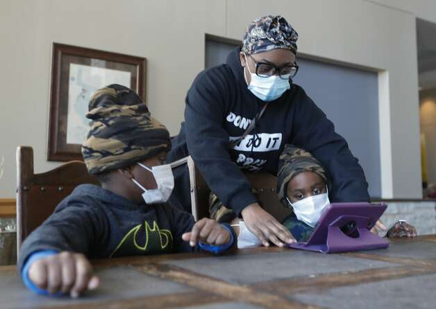 """Angelia Toliver helps set up an iPad for her sons, Zechariah and Mack, at a shelter setup at the Lone Star Convention & Expo Center, Tuesday, Feb. 16, 2021, in Conroe. The family came to the shelter after their home loss power yesterday. """"We're just came here to get warm for a while,"""" Angelia said. """"€œWe'€™re hoping we get power today, but if not we will probably come back to have somewhere warm to sleep."""" Photo: Jason Fochtman/Staff Photographer / 2021 © Houston Chronicle"""