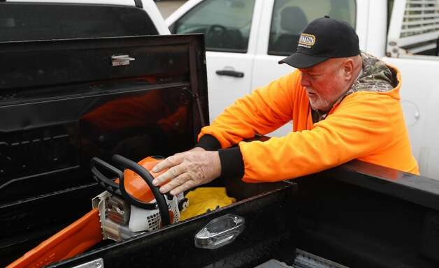 Dennis Stewart places a chainsaw into a Montgomery County vehicle in preparation for any fallen trees as a result of ice, wintery weather expected early next week, Friday, Feb. 12, 2021, in Willis. Photo: Jason Fochtman/Staff Photographer / 2021 © Houston Chronicle