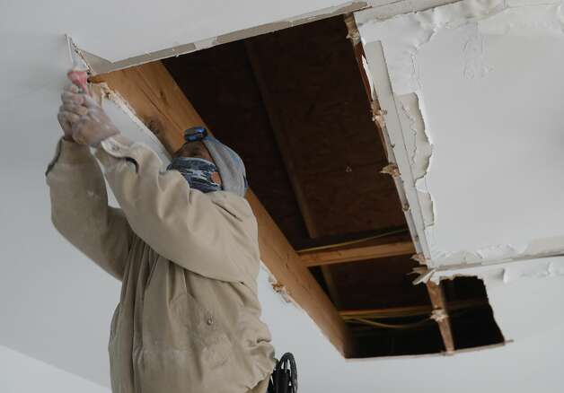 Manyu Torres stripes out sheetrock after a women's pip burst above her garage, damaging her car, roof and ceiling on Thursday, Feb. 18, 2021. Photo: Jason Fochtman/Staff Photographer / 2021 © Houston Chronicle