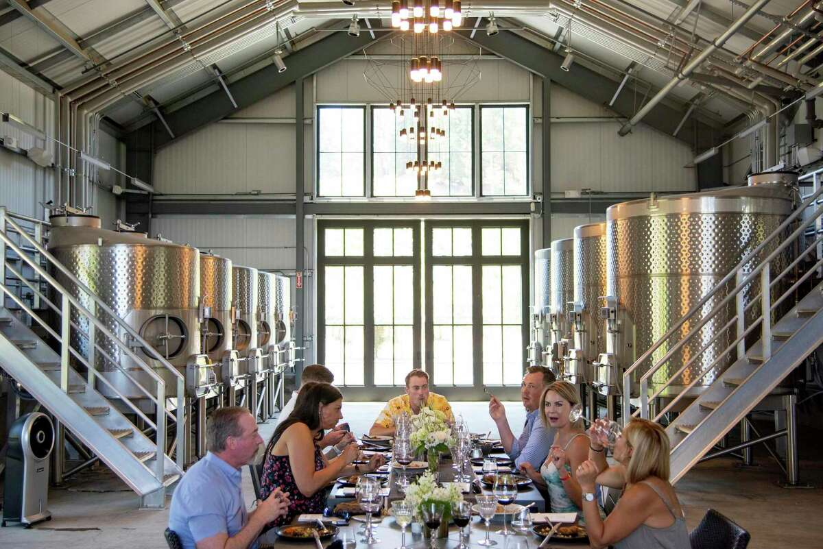 A group of business colleagues celebrates a couple's recent engagement with a custom wine experience at Theorem Vineyards on Diamond Mountain in Calistoga.