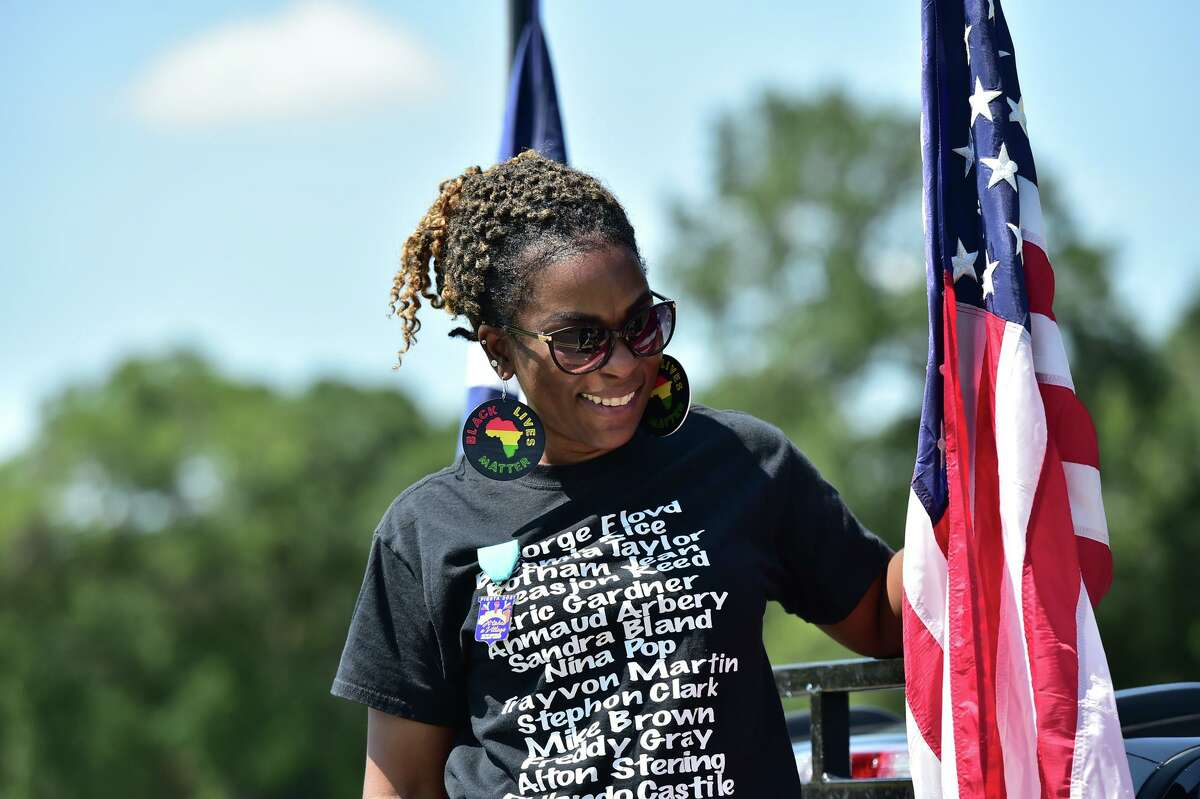 Dasha Nicholson posts her flag Saturday during the second day of the Juneteenth Festival at Comanche Park.