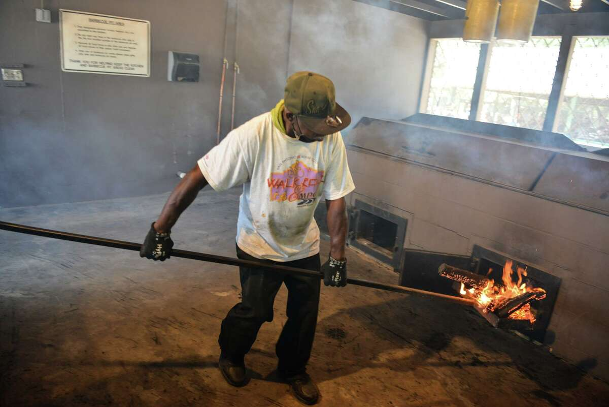 Roland Mackey shovels coals onto the pits to cook over 2500 chickens Saturday at Comanche Park.
