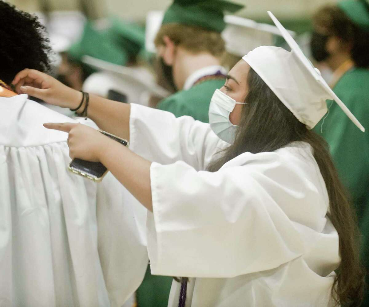 Kellie Jackson makes a gown adjustment prior to the start of the New Milford High School graduation ceremony. Saturday, June 19, 2021