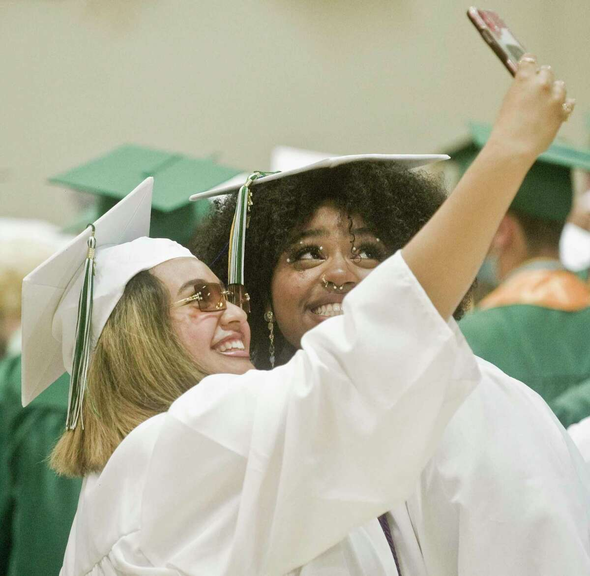 Karina Batista and Jordyn Ingram save the moment prior to the start of the New Milford High School graduation ceremony. Saturday, June 19, 2021