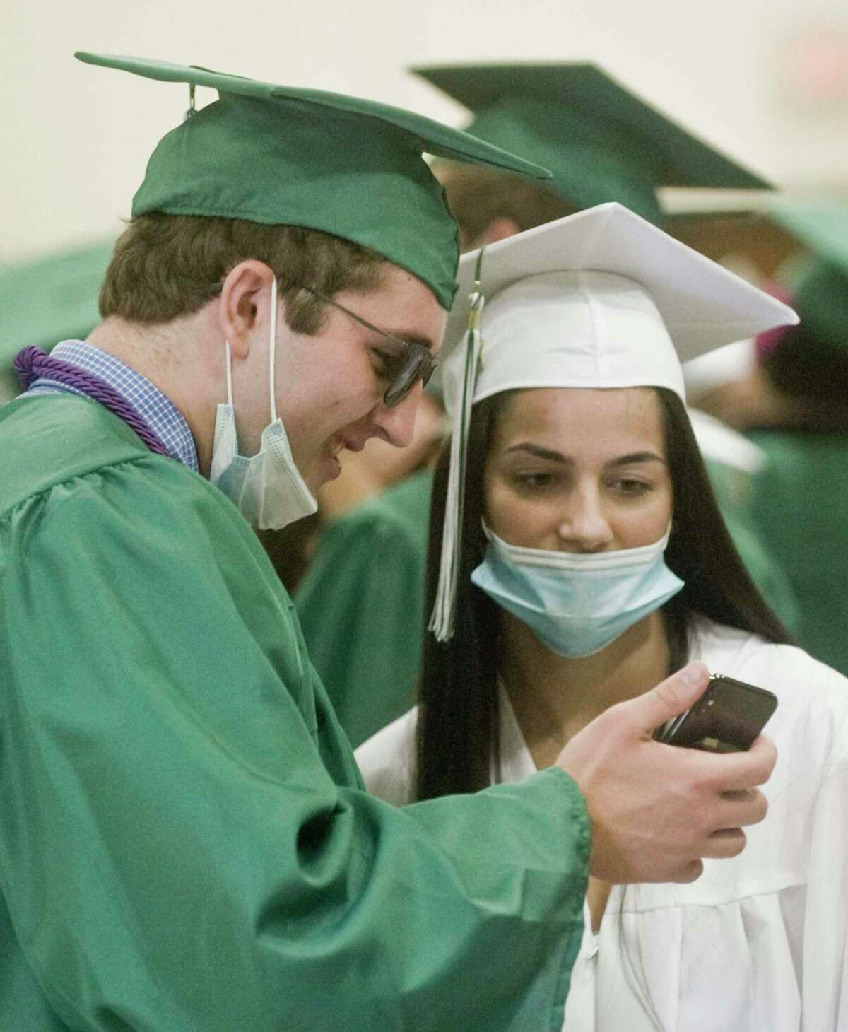 Daniel Rizvic and Thea Spinner check out a phone photo prior to the start of the New Milford High School graduation ceremony. Saturday, June 19, 2021