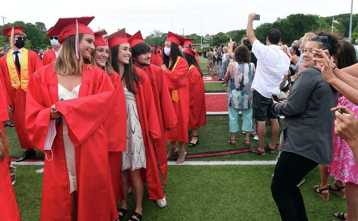 Graduates pose for photographs as they march into graduation ceremonies at Branford High School's James L MacVeigh Alumni Athletic Complex on June 18, 2021.