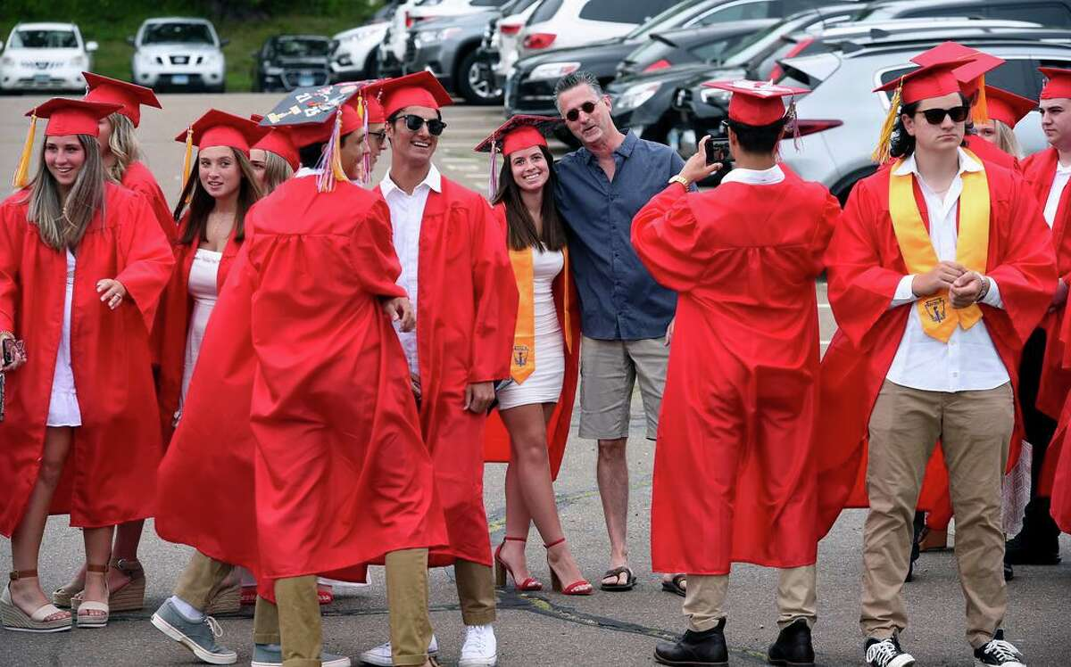 Graduates take photographs while waiting to march into graduation ceremonies at Branford High School's James L MacVeigh Alumni Athletic Complex on June 18, 2021.