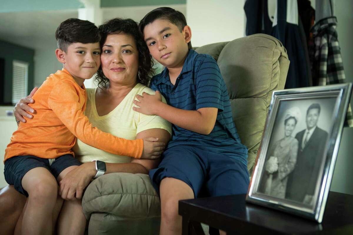 Sunny Astorga poses with sons, Jude Swilley, 7, and Keen Swilley, 10. Astorga lost her father, Ysidro Astorga Jr., in the family photo on the side table, in 2008.