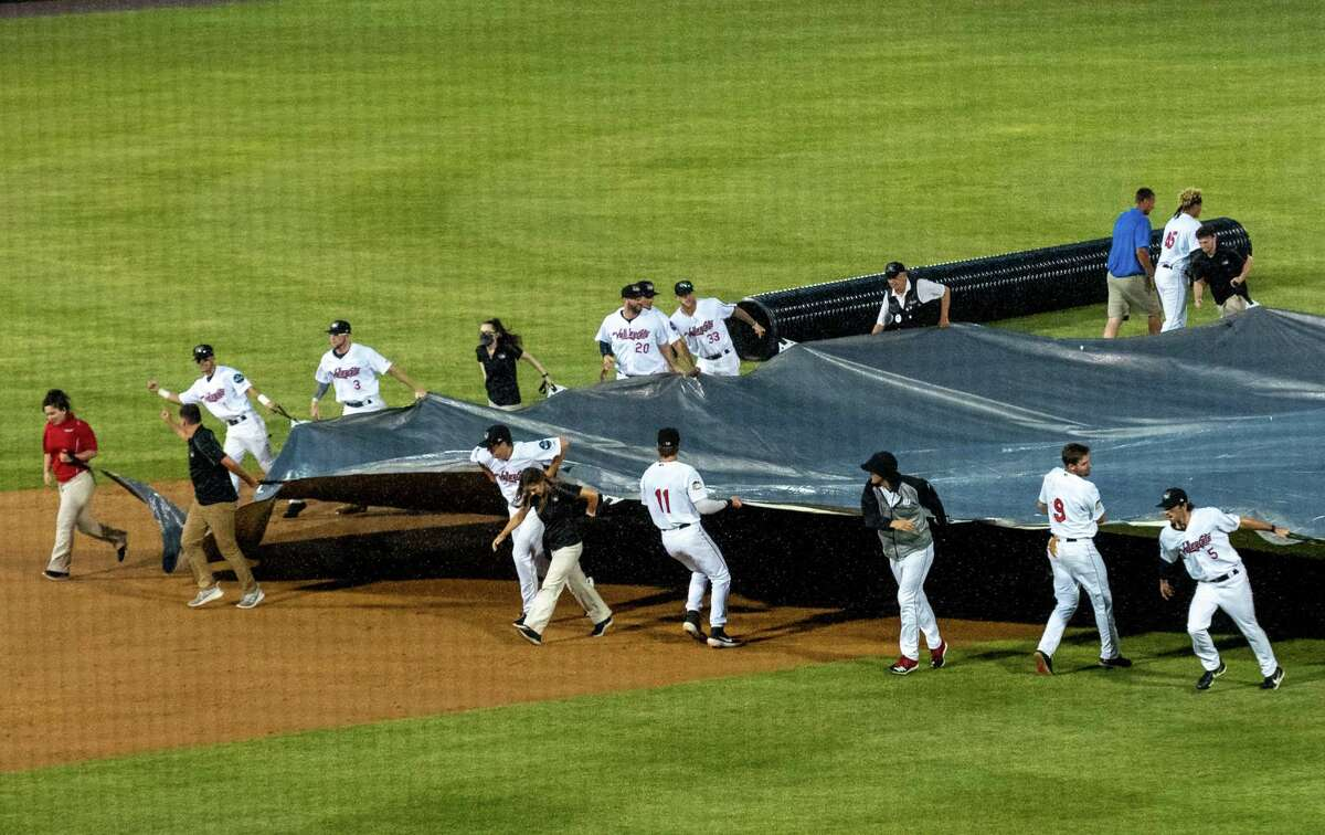 The Tri-City ValleyCats help roll out the tarp during an approximately 30-minute rain delay against the Sussex County Miners at the Joseph L. Bruno Stadium on the Hudson Valley Community College campus in Troy, NY, on Saturday, June 19, 2021 (Jim Franco/Special to the Times Union)