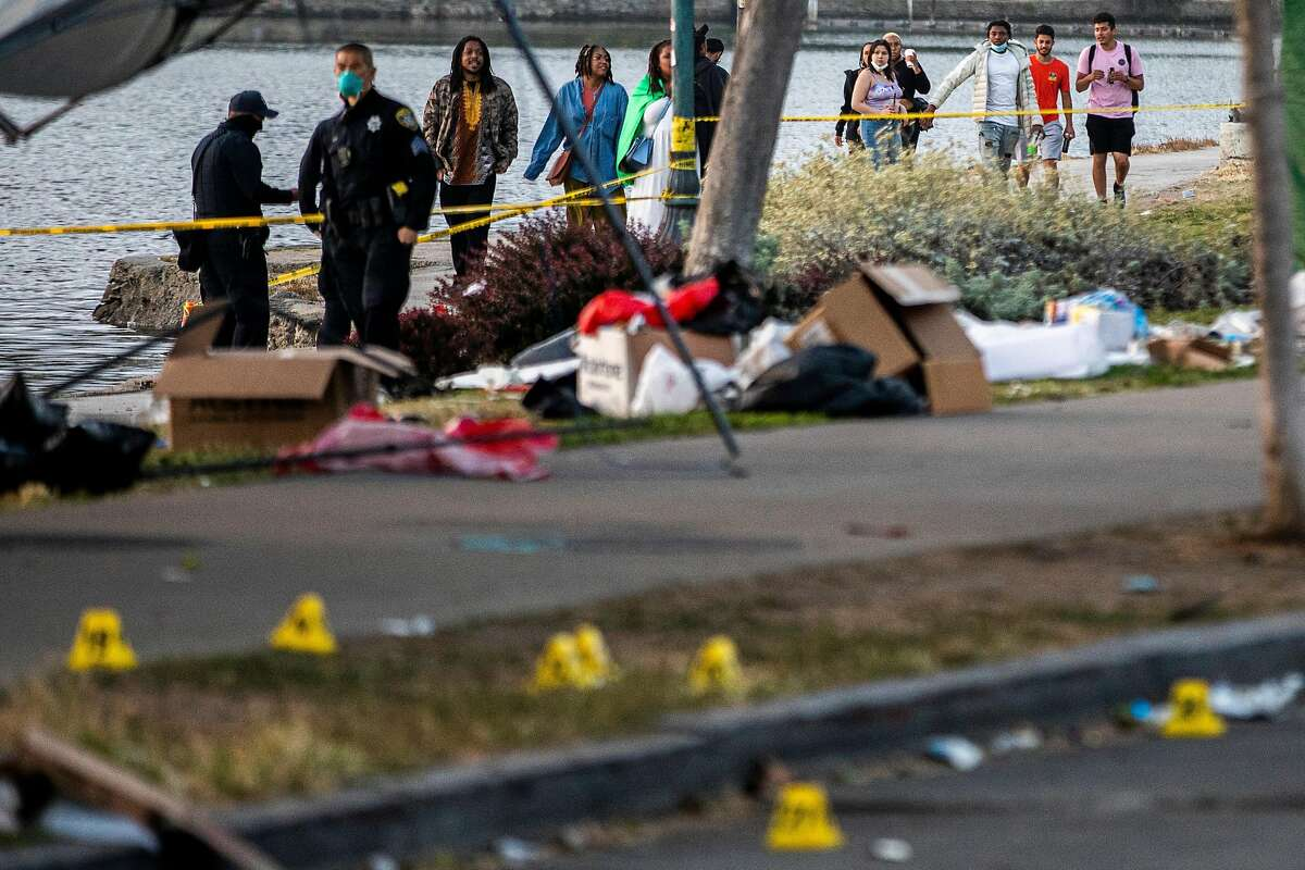 People behind police tape watch as police investigate the scene of a fatal shooting along Lakeshore and Brooklyn avenues in Oakland.