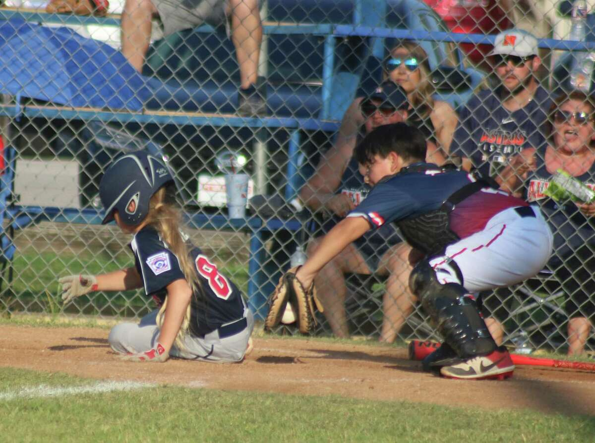 NASA Area Little League's Reagan Risinger (8) scores just ahead of the tag attempt, giving his teammates a 2-1 lead in the fourth in Dickinson Friday night.