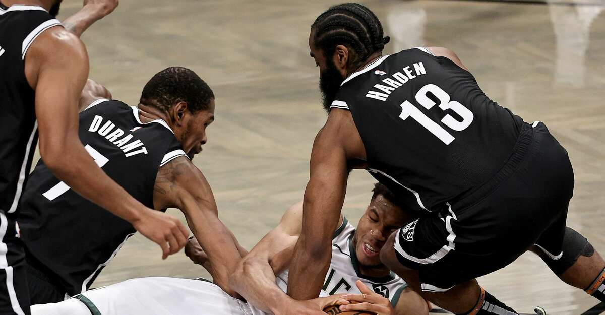 Giannis Antetokounmpo #34 of the Milwaukee Bucks fight for the loose ball with Kevin Durant #7 and James Harden #13 of the Brooklyn Nets in the first half during game seven of the Eastern Conference second round at Barclays Center on June 19, 2021 in the Brooklyn borough of New York City. (Photo by Elsa/Getty Images)