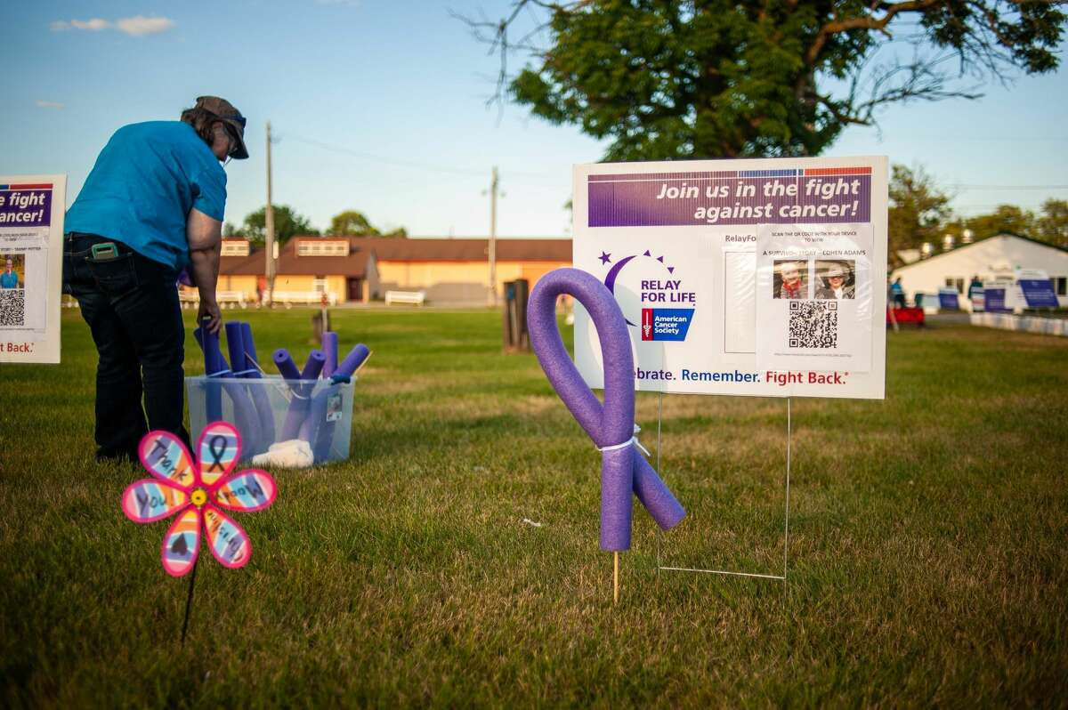 Midland resident Pat Carey, member of Team Cure, places a cancer ribbon by a sign for the Midland County Relay for Life, June 19, 2021 at the Midland County Fairgrounds.