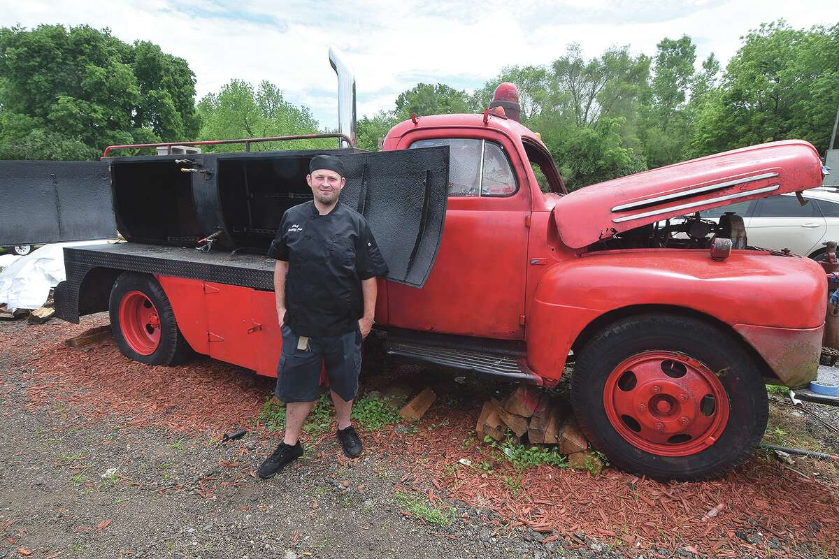 Buddy Fore with a 1949 firetruck he has converted into a meat smoker.