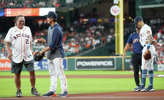 Houston Astros dads Donald Greinke, left, and Carlos Correa Sr react after throwing out the ceremonial first pitch to their sons before the Astros take on Chicago White Sox at Minute Maid Park in Houston on Sunday, June 20, 2021. Photo: Elizabeth Conley, Staff Photographer / © 2021 Houston Chronicle