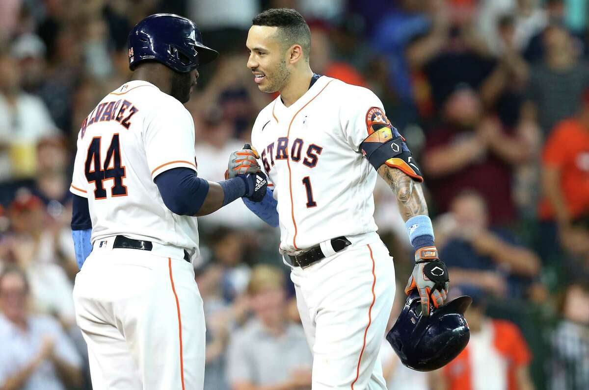 Houston Astros shortstop Carlos Correa (1) is congratulated by designated hitter Yordan Alvarez (44) after hitting a solo home run in the fourth inning at Minute Maid Park in Houston on Sunday, June 20, 2021.