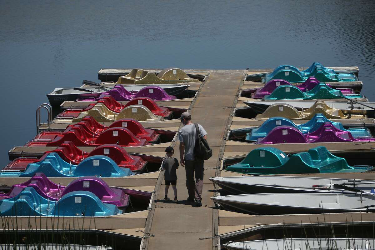 Four-year-old James Heron and his father, Simon Heron, walk on the dock as they choose a paddle boat to take out at the Lafayette Reservoir Recreation Area on Friday.