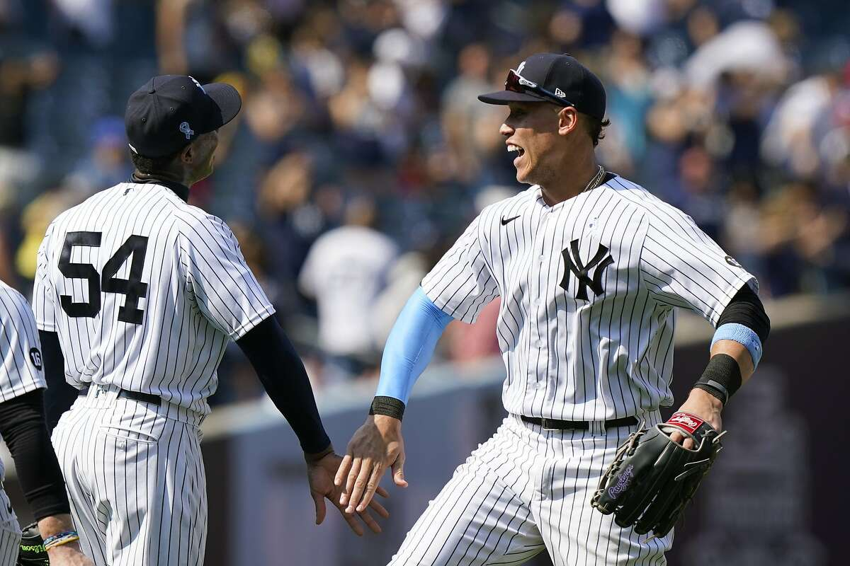 New York Yankees center fielder Aaron Judge, right, celebrates with closer Aroldis Chapman after completing a triple play to defeat the Oakland Athletics in a baseball game, Sunday, June 20, 2021, at Yankee Stadium in New York. (AP Photo/Kathy Willens)