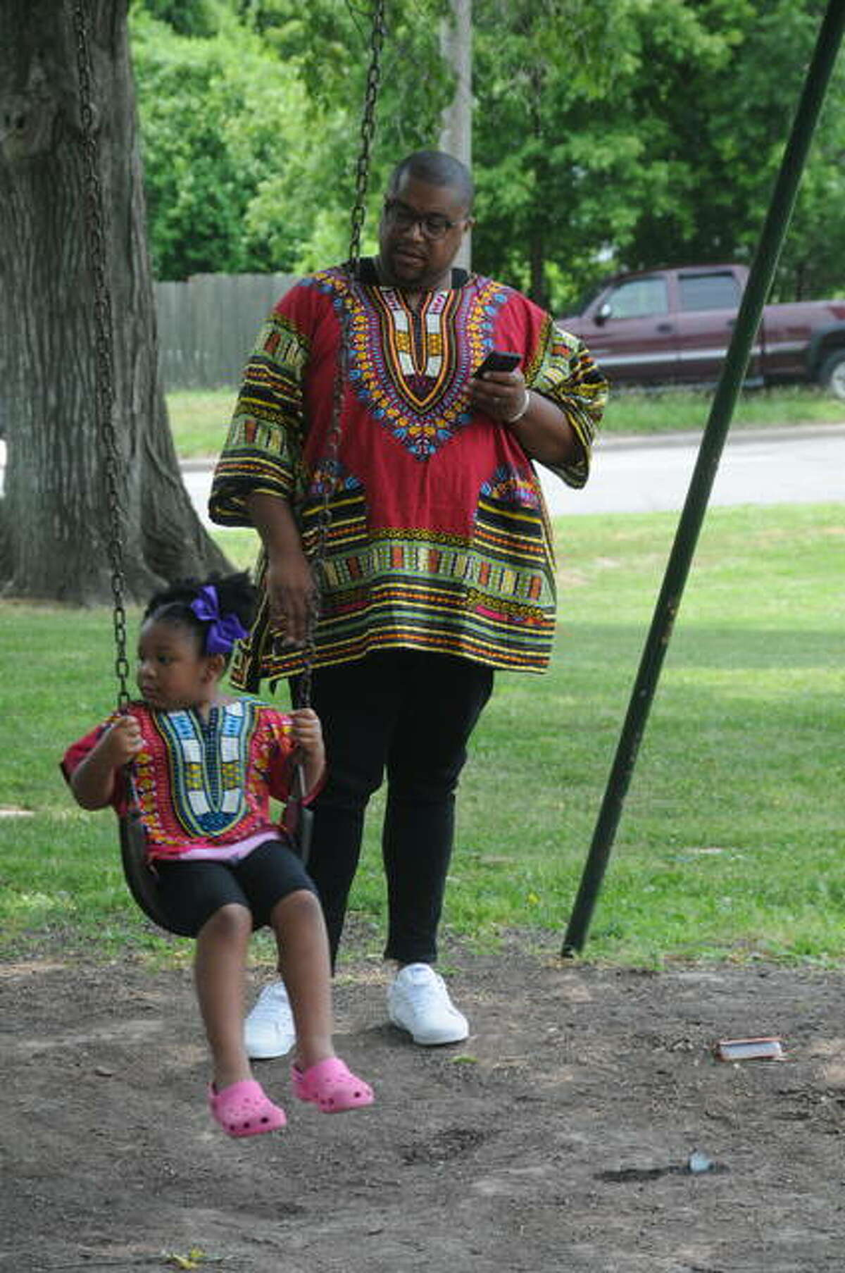 Mark Goins and his 4-year-old daughter, Mayla, relax during the Alton Juneteenth Celebration at James Killion Park in Alton.