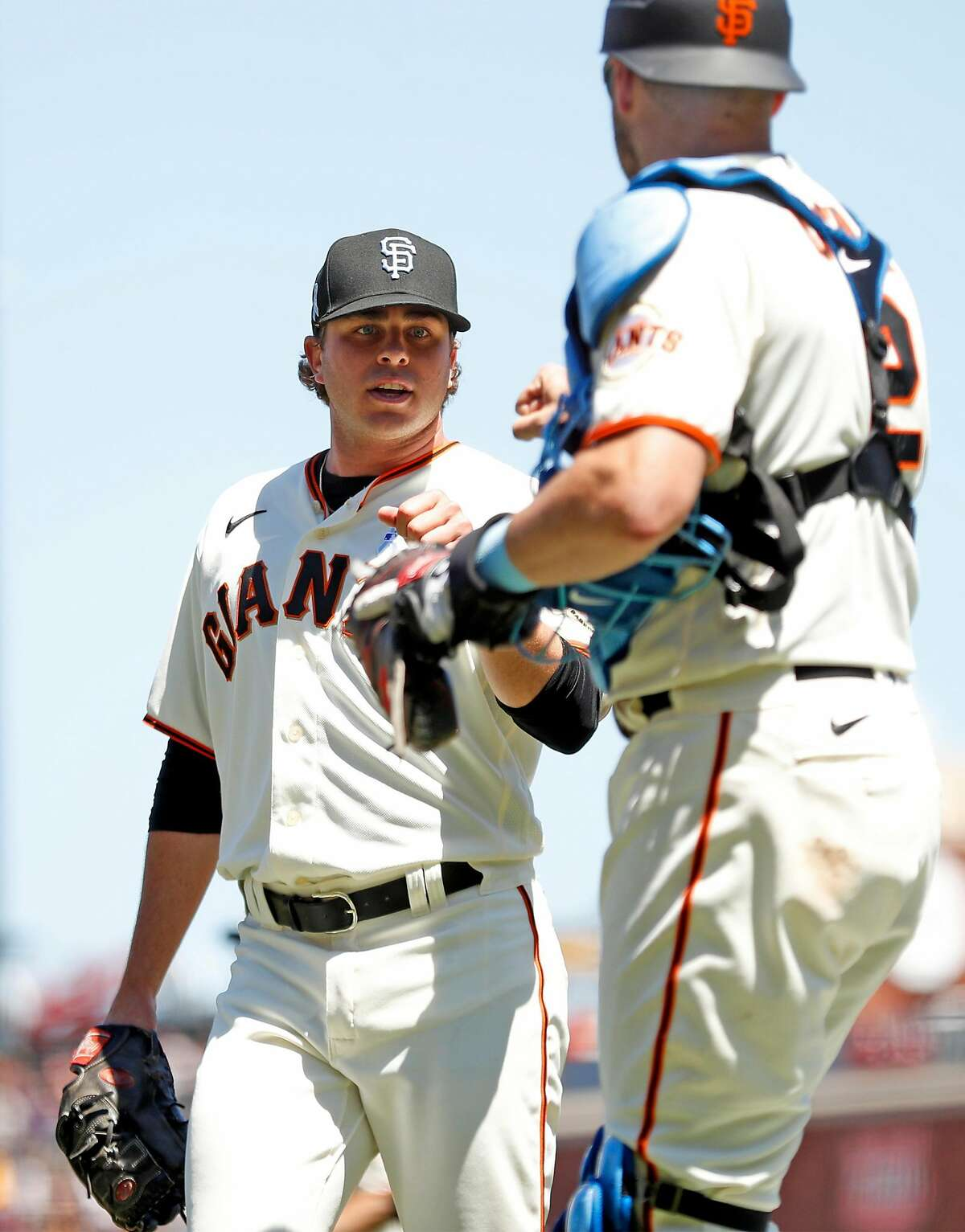 San Francisco Giants' starting pitcher Sammy Long fist bumps catcher Curt Casali after retiring the Philadelphia Phillies in top of 6th inning during MLB game at Oracle Park in San Francisco, Calif., on Sunday, June 20, 2021.