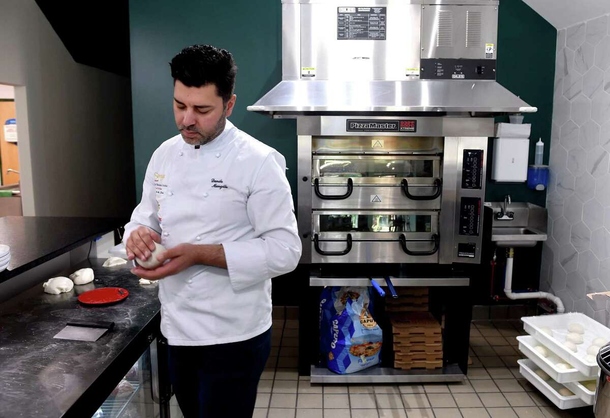 Danilo Mongillo, co-owner and executive chef at Strega, prepares pizza dough at the restaurant in Milford on June 18, 2021.