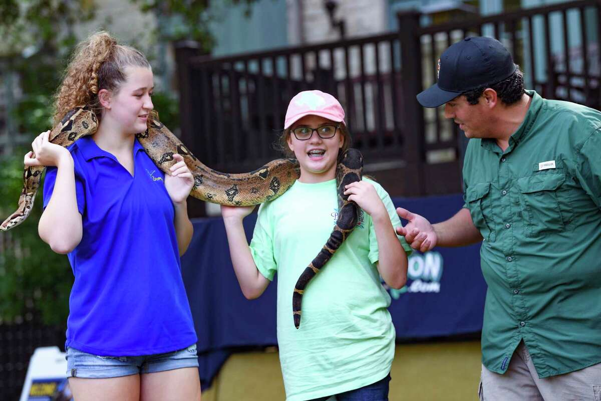 """Kylie Meyer, left, and Clay Carabajal, right, introduce Sophia Gibson, middle, to a Colombian red-tailed boa during a show at the Hyatt Hill Country Golf Club on Wednesday, June 9, 2021. Carabajal is an animal ambassador at SeaWorld San Antonio and host of the new YouTube series, """"The Wild Side."""""""