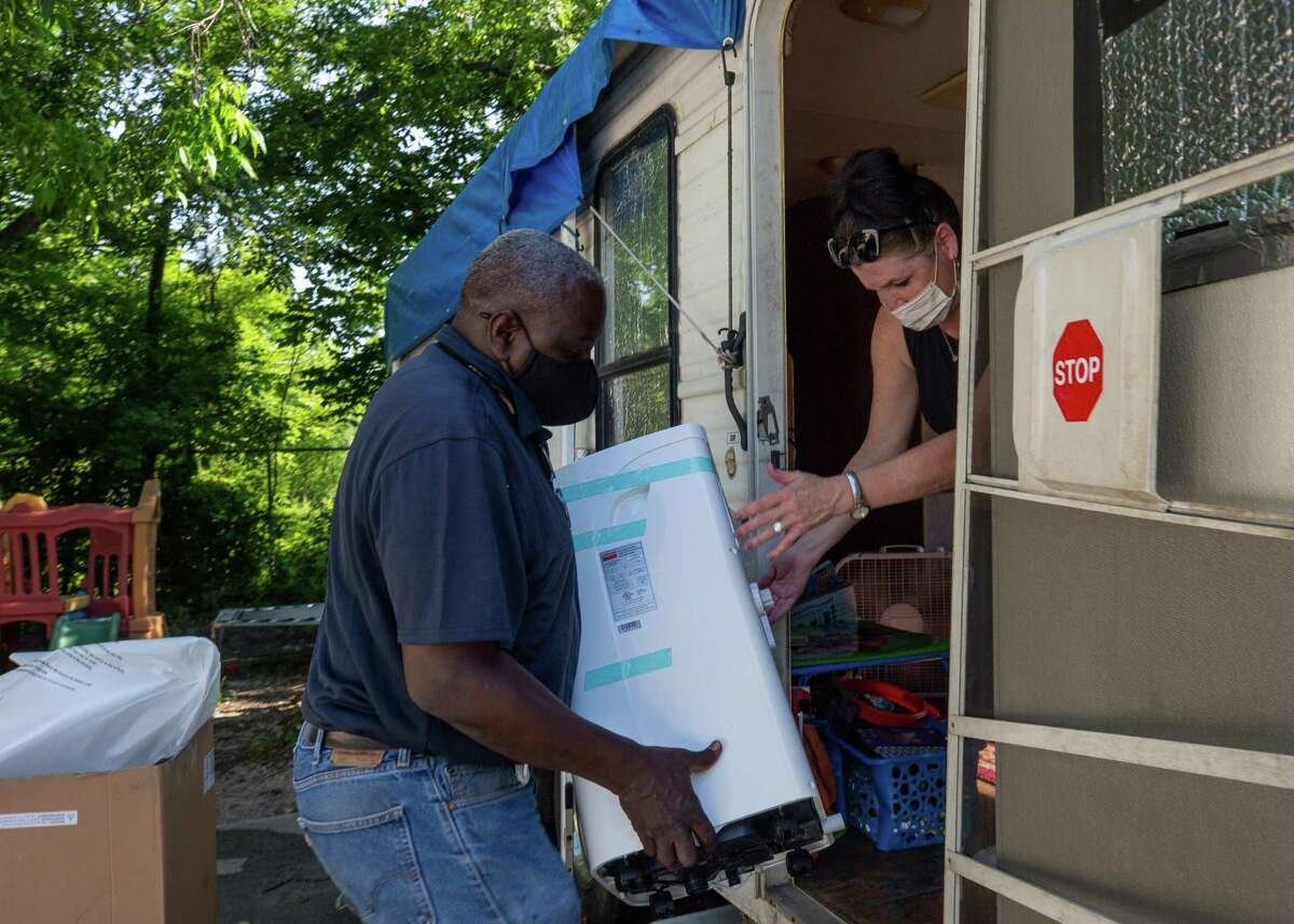 Greg Harrison, with the City of Houston, delivers a portable air conditioning unit to Mary Smith on Friday, June 18, 2021, in Houston.