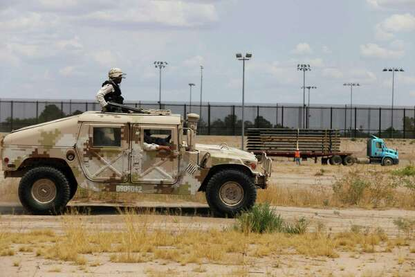 Members of the Mexican National Guard patrol along the Rio Grande, near the construction site of a new section of the border wall between El Paso, Texas, and Ciudad Juarez, Mexico, on Aug. 17, 2020. Texas Gov. Greg Abbott on Wednesday fleshed out his plan to erect a barrier along the state's border with Mexico and begin arresting migrants. (Herika Martinez/AFP via Getty Images/TNS)