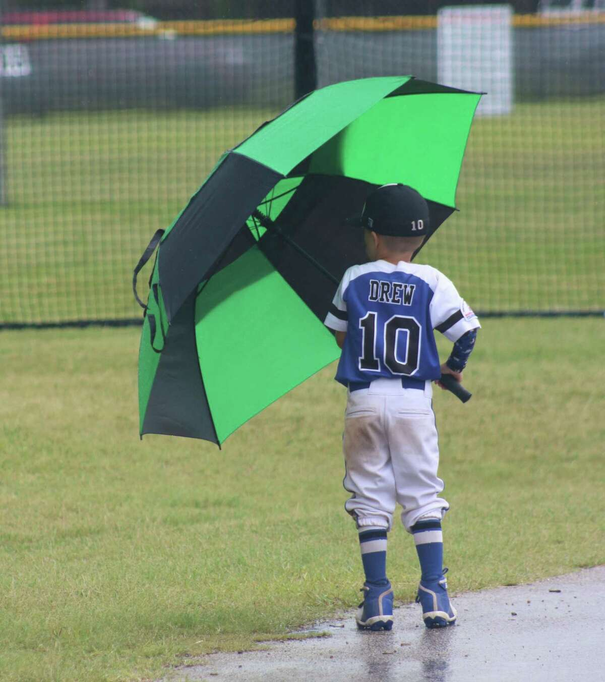 Friendswood Blue Shetland outfielder Jacob Drew stayed dry with the help of his big umbrella after a brief heavy downpour hit Renwick Park Sunday afternoon. Jacob and Co. defeated Crosby Sunday 25-15, forcing a second title game in the Blue Bracket.