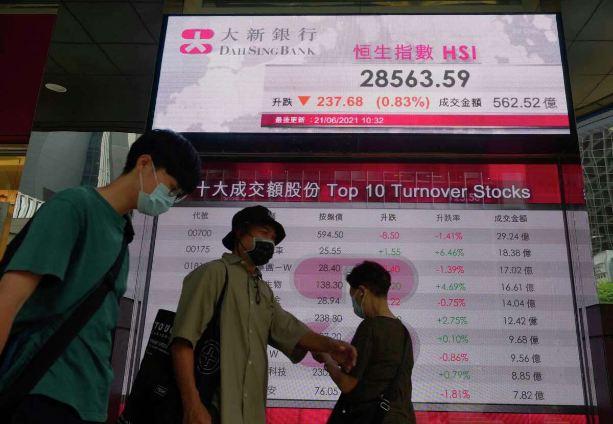 People walk past a bank's electronic board showing the Hong Kong share index at Hong Kong Stock Exchange Monday, June 21, 2021.
