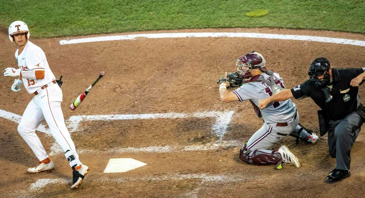 Home plate umpire Steve Mattingly calls out Texas's Mitchell Daly on a pitch from Mississippi State's Landon Sims as Mississippi State catcher Logan Tanner holds the ball in position in the ninth inning of a College World Series baseball game, Sunday, June 20, 2021, in Omaha, Neb.