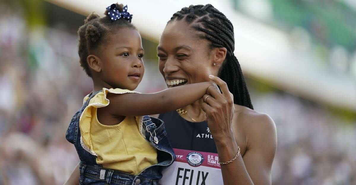 Allyson Felix celebrates after her second place finish in the women's 400-meter run with her daughter Camryn at the U.S. Olympic Track and Field Trials Sunday, June 20, 2021, in Eugene, Ore.(AP Photo/Ashley Landis)