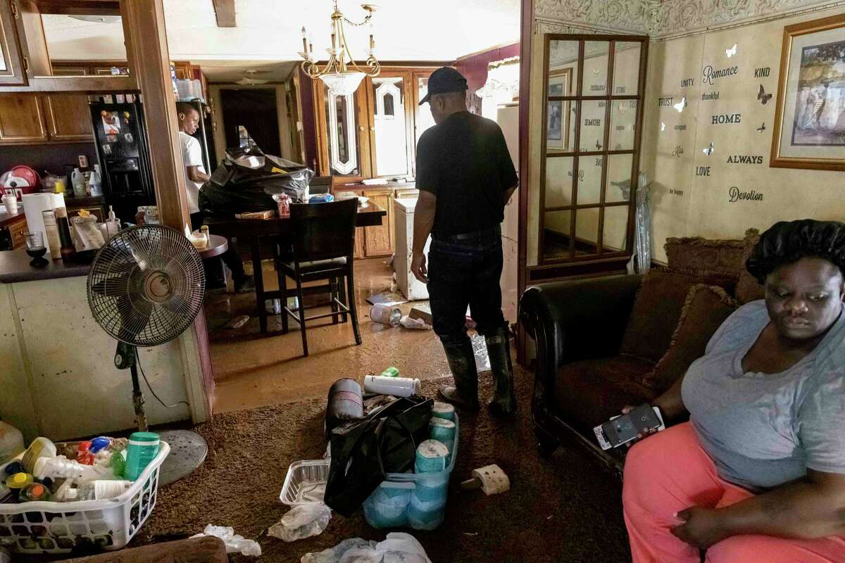 Percy Ross, center, the owner, works through his flood-damaged home as his son, Michael Roberts, left, seeks to recover valuables after heavy flooding Saturday night, in Northport, Ala., Sunday, June 20, 2021. At right is Ross's daughter, Candy Roberts.